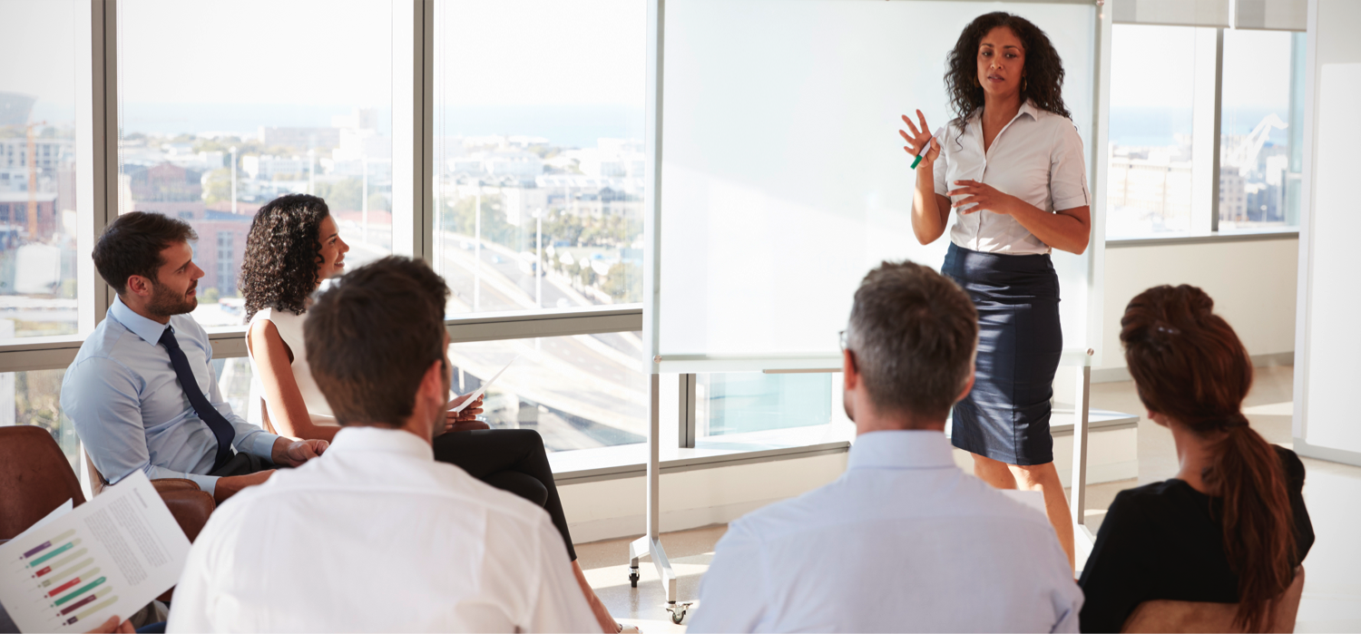 Woman in front of whiteboard gesturing to colleagues in a meeting