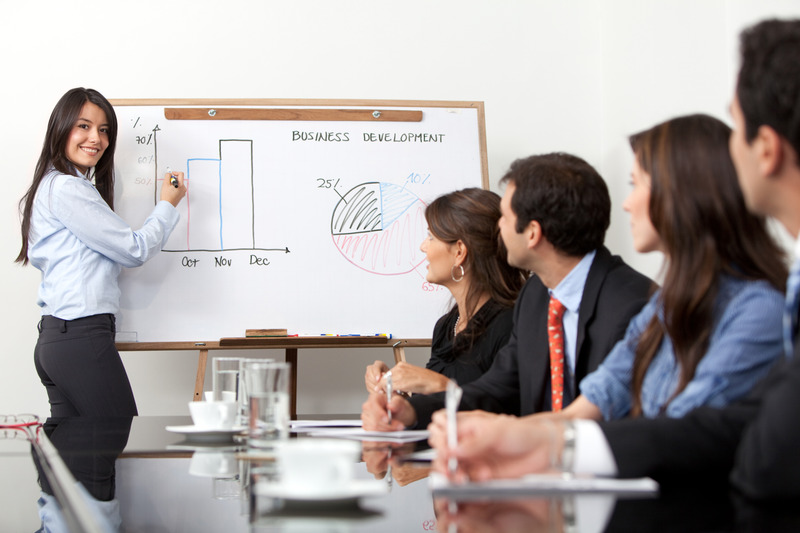 Woman presenting graphs to colleagues in business meeting
