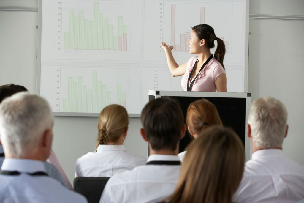 Woman presenting bar graph to colleagues