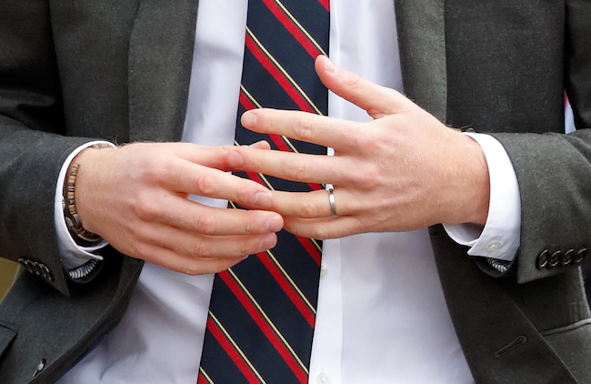 Nervous hands of suited man with wedding band.