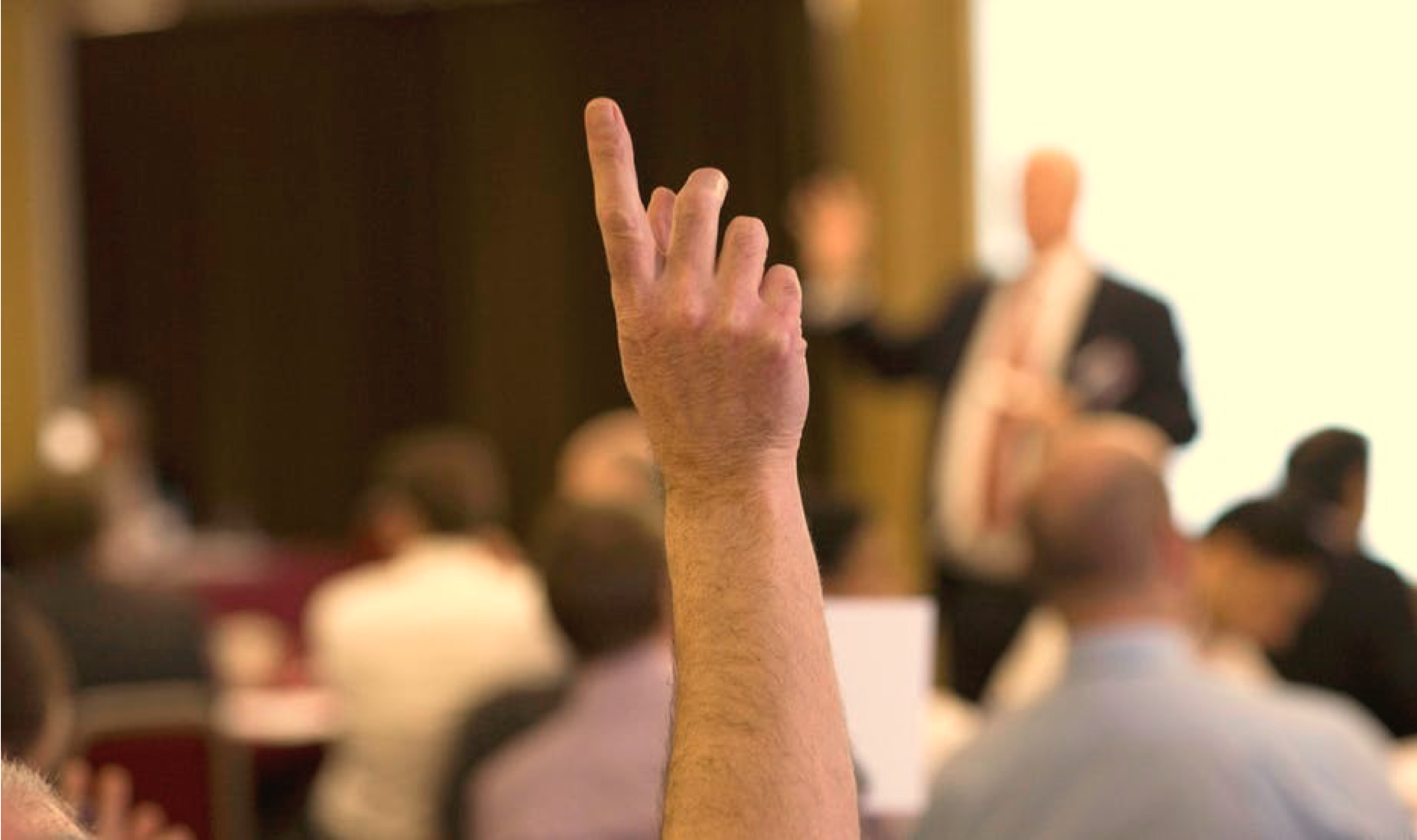 Hand in the air gesturing question at public speaking conference
