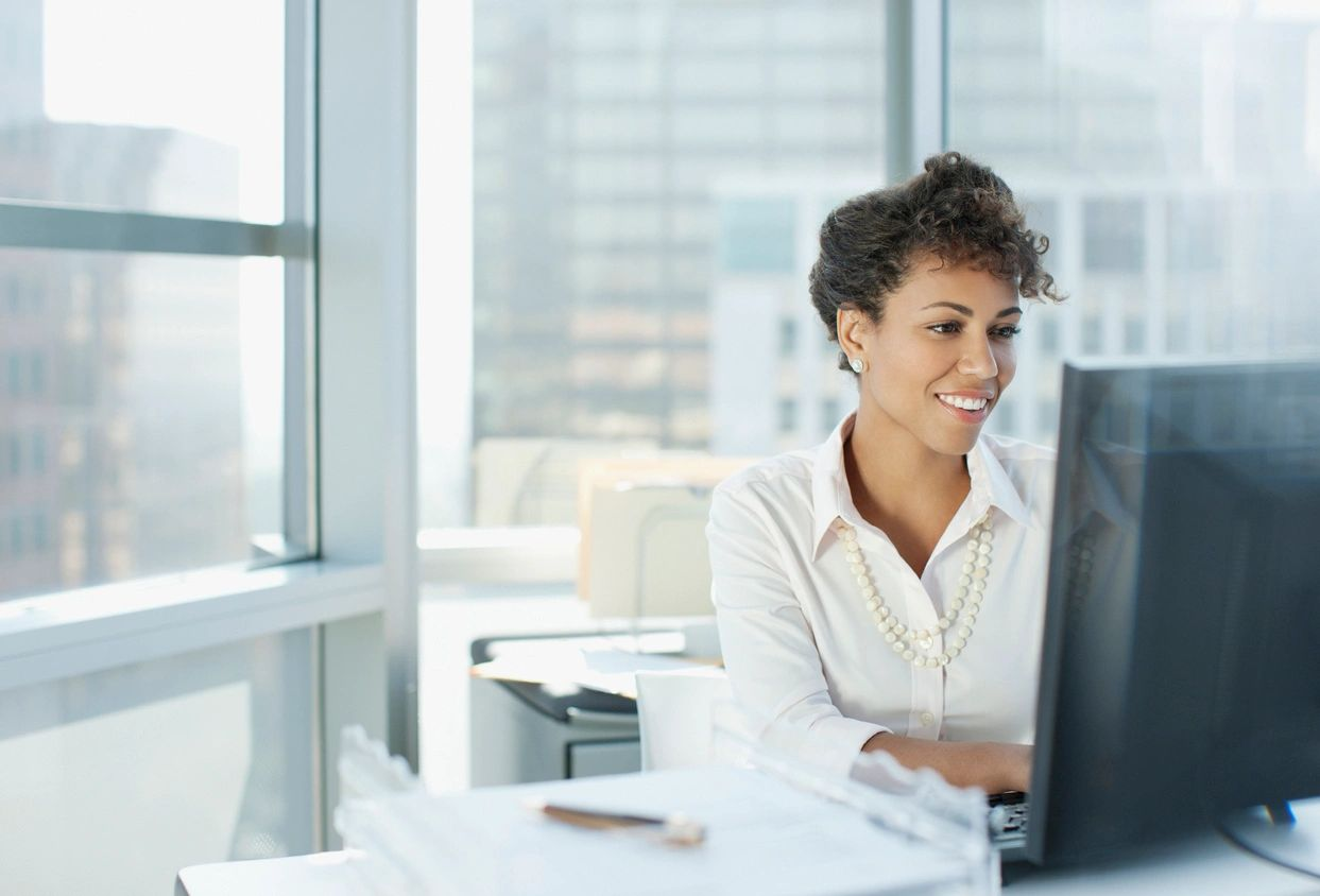 Woman smiling using computer for Zoom meeting